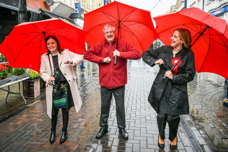Mark Drakeford smiles an bumps elbows with two women, one with a red rosette, all carrying red umbrellas.