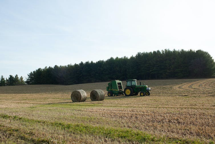 A tractor and two round bales of hay on a sunny day in Wellington County, Ontario