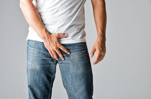 Un homme avec sa main sur son pantalon, à la hauteur de son pénis