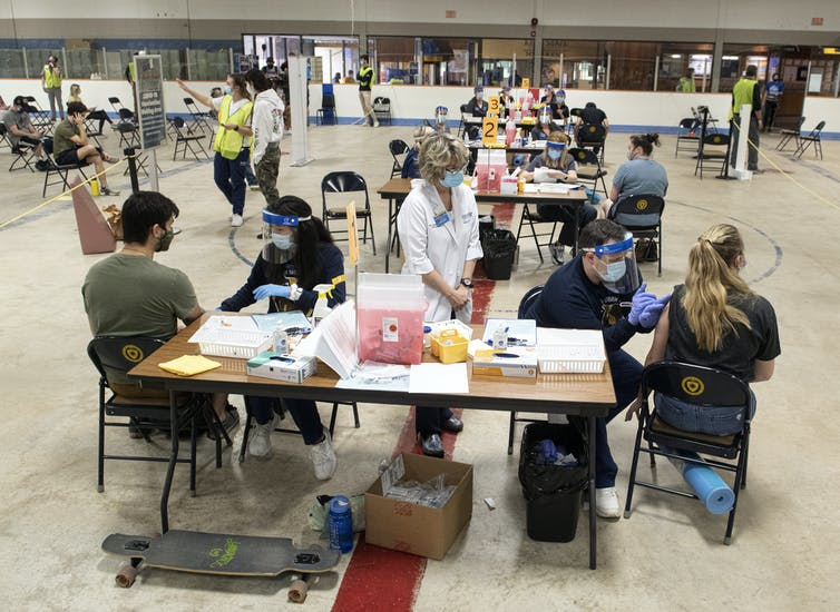 Students and medical personal at tables in a large open area.