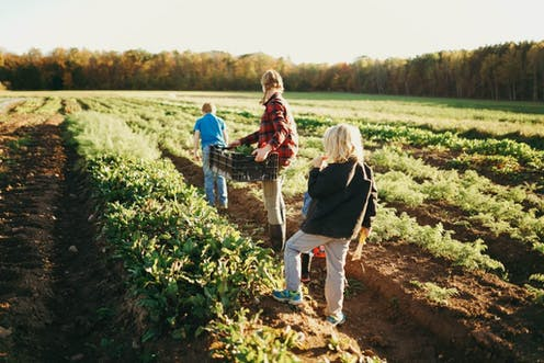 Kat Becker and two of her children in the field.