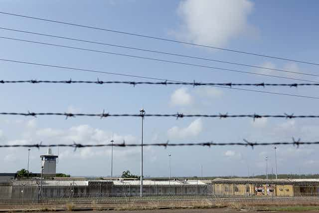 A barbed wire fence in focus, with the Don Dale Youth Detention Centre in the background.