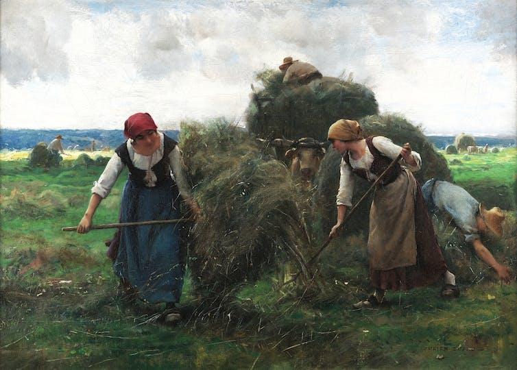 Two women baling hay.