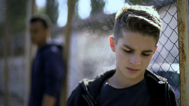 A teenage boy leans against a fence, appearing despondent.