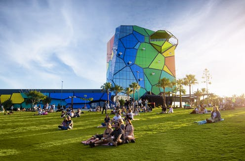 A colourful gallery rises above green grass