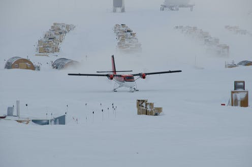A light aircraft lands on a snow field at the South Pole with boxes of supplies