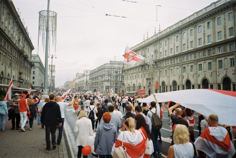 A crowd carrying red and white flags protests on a Belarussian street in winter