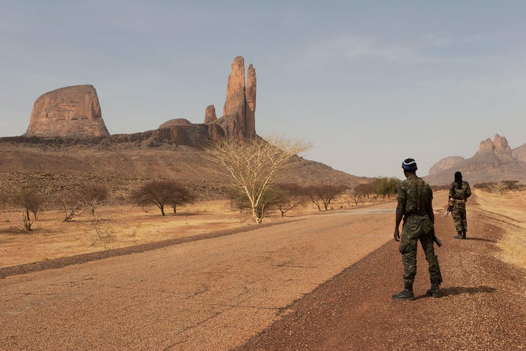 Armed soldiers patrol an empty road in barren countryside in central Mali