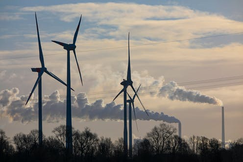 Wind turbines with industrial chimney in background