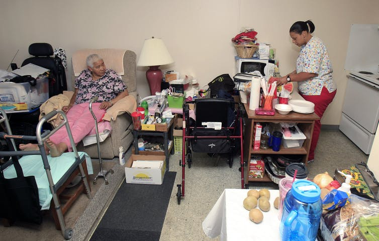 An elderly woman lies in a bed as a home care aide prepares some food.