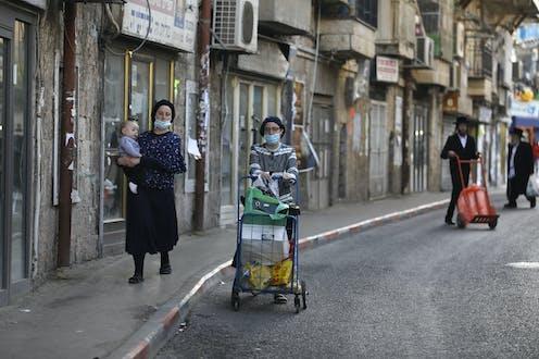 Ultra-Orthodox women walk down street in Jerusalem