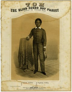 title reads TOM The Blind Negro Boy Pianist Only 10 Years Old and has an illustration of a boy in dark jacket with white collar and cuffs, standing with his arm on a table. He holds his hat in the other hand.
