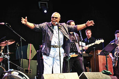 Musician Sam Moore stands behind a microphone wearing sunglasses with his arms raised