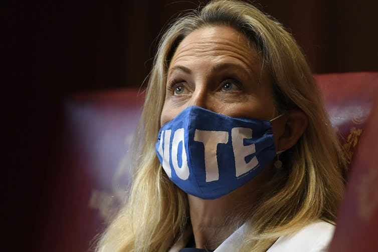 A woman looking up wearing a blue mask with the word 'VOTE' on it.