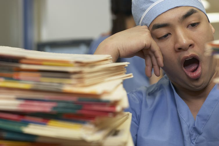 health care worker yawning next to stack of medical records