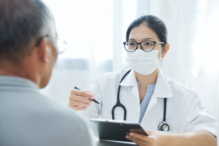 A family doctor in a face mask talking to a patient