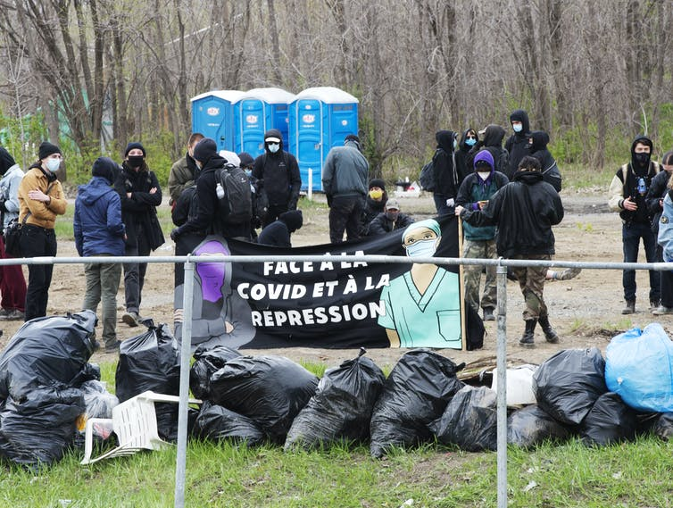 People around homeless camp, garbage bags in the front and portable toilets in the background.
