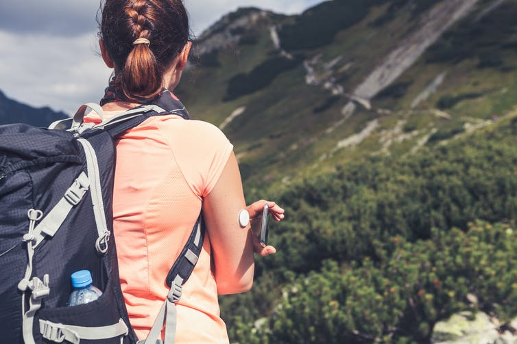 Woman in the wild, wearing a backpack and a sensor on her finger