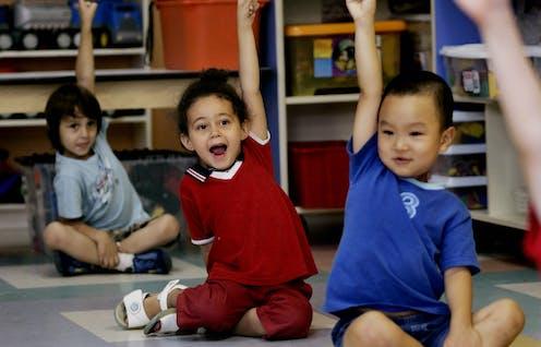 Children with their hands raised.