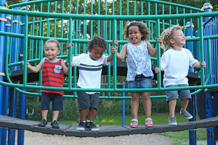 Children standing on  playground bridge.