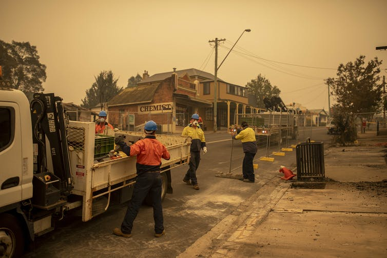 People help erect fences in a bushfire-affected town.