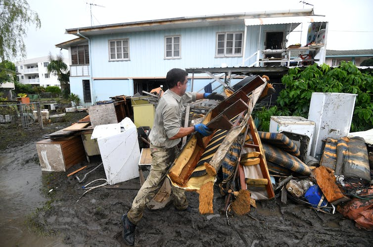 Members of a flood-affected community clean up.