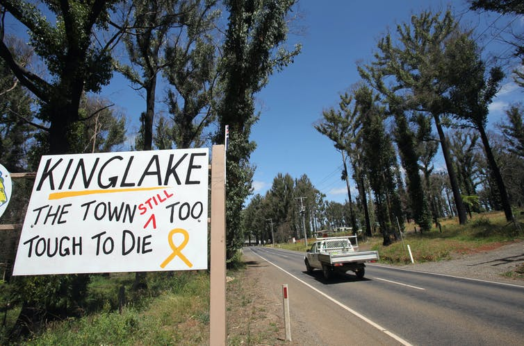 A sign outside a fire affected town says 'Kinglake, the town still too tough to die'.