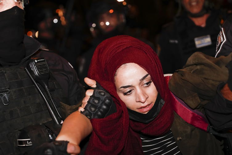 Palestinian protester is arrested.