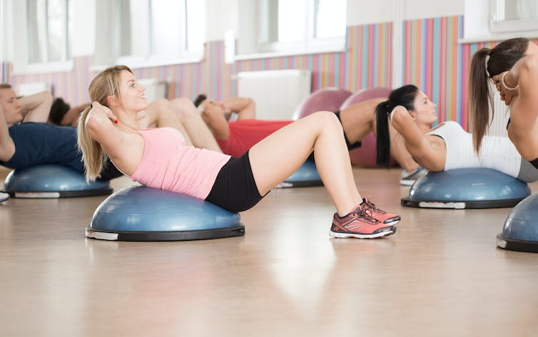 People performing sit-ups on BOSU balls in an exercise class.