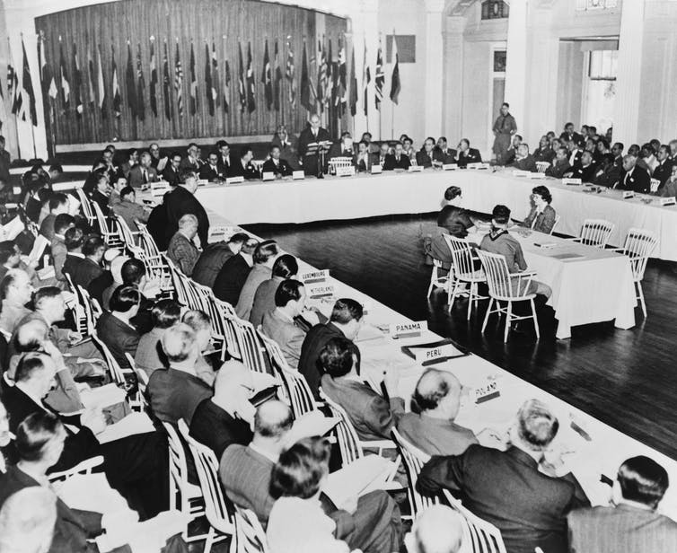 Black and white photo of delegates seated around horseshoe table with flags in the background.