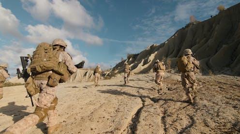 Military personnel in desert.
