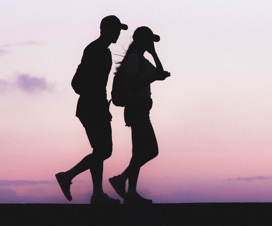 Silhouettes of man and woman walking at twilight