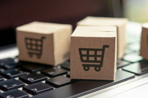 Cardboard cubes with trolley picture sat on a laptop keyboard