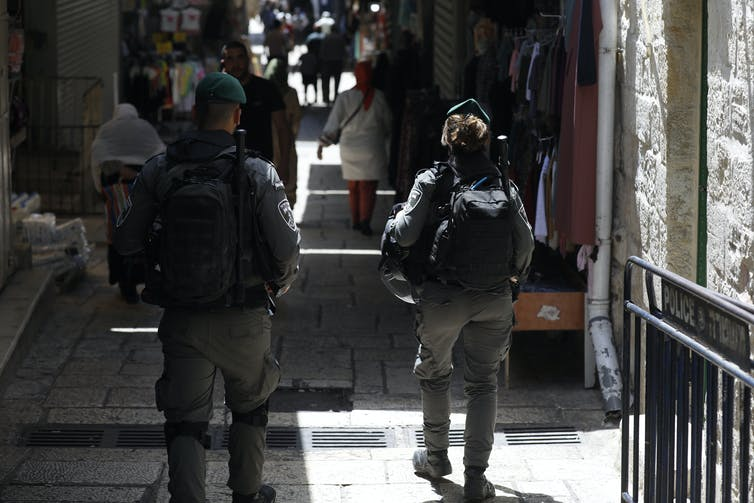 Back view of two members of Israel's border force patrolling an alley in Jerusalem's Old City with civilians in the background.