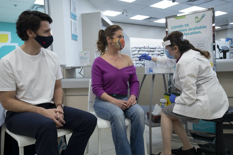 Sophie Grégoire Trudeau gets her AstraZeneca vaccination as Justin Trudeau looks on.
