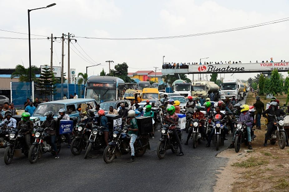 Commercial motorcycle riders in front of vehicular traffic on a road.