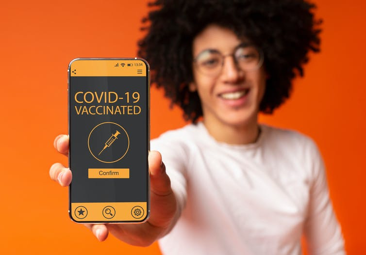 person holding a mobile phone displaying a Covid-19 vaccinated message