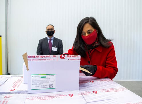 Minister of Public Services Anita Anand wearing a red face mask, opening a box of vaccine.