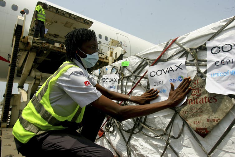 A person in a reflective vest and a face mask examining a crate with a COVAX label