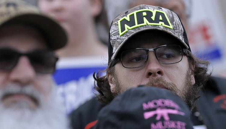 A man in a cap with the NRA logo looks askance.