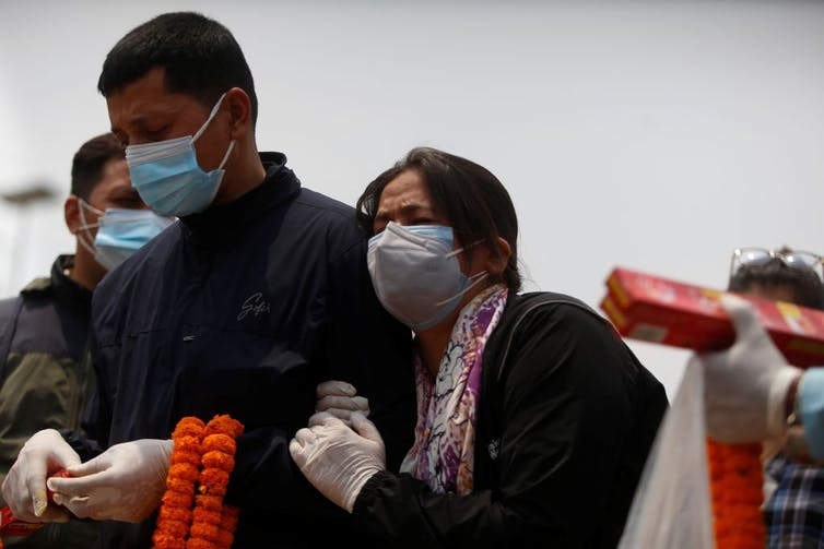 A woman and a man mourn for a family member who died from the COVID-19 in Kathmandu, Nepal
