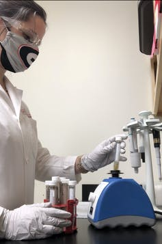 masked scientist holding various test tubes
