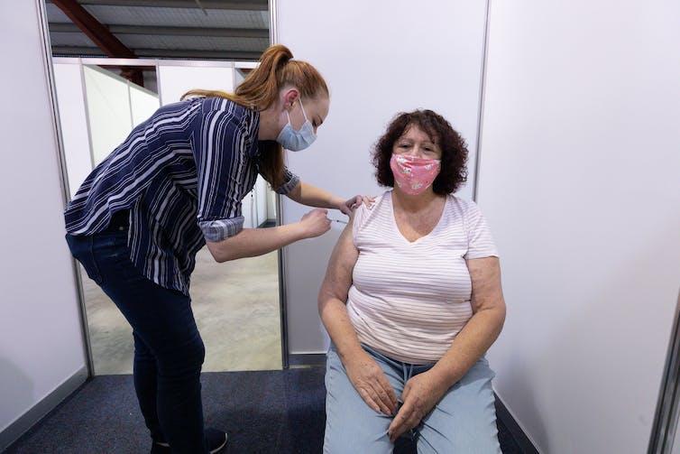 A nurse vaccinating a person with the AstraZeneca COVID-19 vaccine