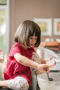 A little girl in a red dress sits on a counter top stirring cake mixture to make cupcakes