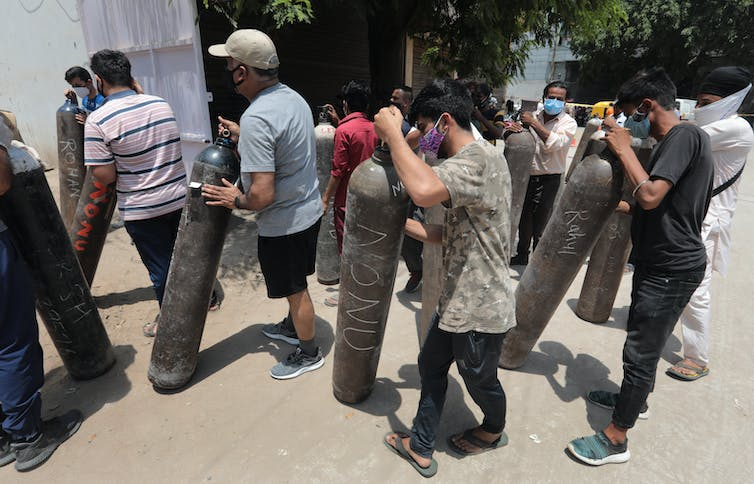 People queuing to get their oxygen tanks refilled, New Delhi, India, May 11 2021.