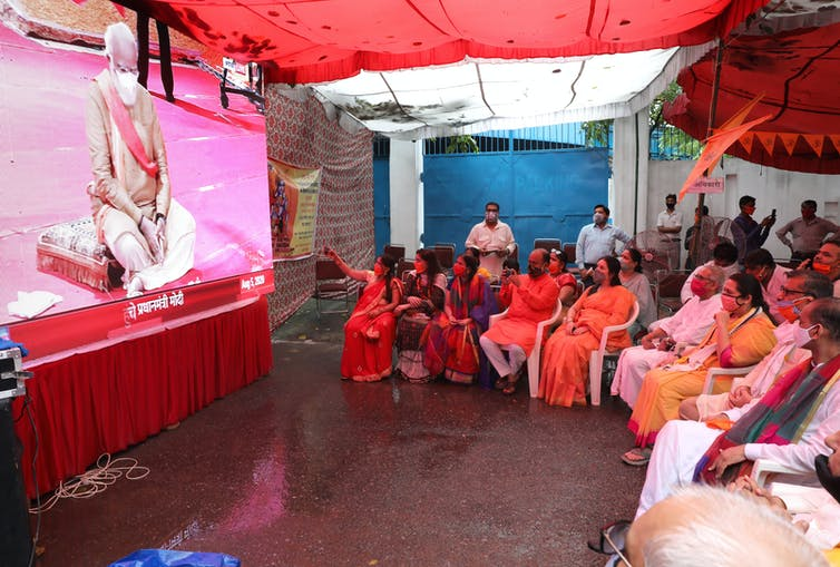 A roomful of seated spectators watches a big screen as India prime minister, Narendra Modi, lays the foundation stone for a new Hindu temple in Ayodhya, August 2021.