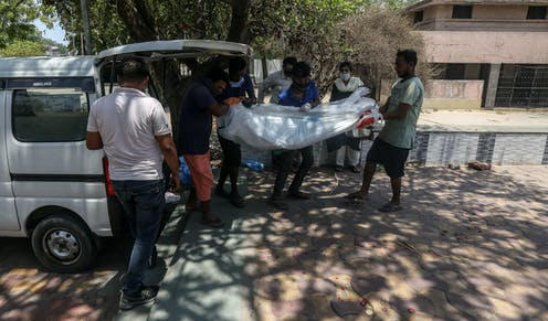 Indian citizens carrying the shrouded body of a COVID victim into the back of a van on the way to a crematorium, Ahmedabad, India, May 11 2021.