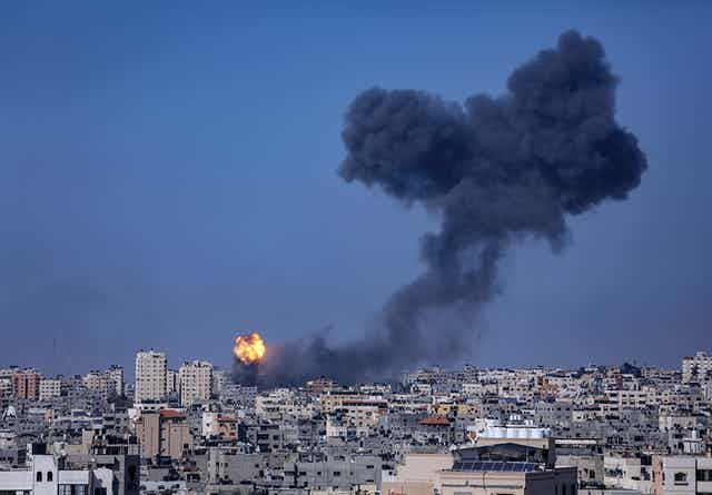 Skyline of Gaza City showing a tower block on fire.