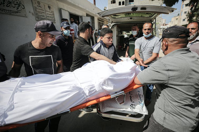 A group of men load a body wrapped in a sheet into the back of an ambulance, Gaza City, May 2021.