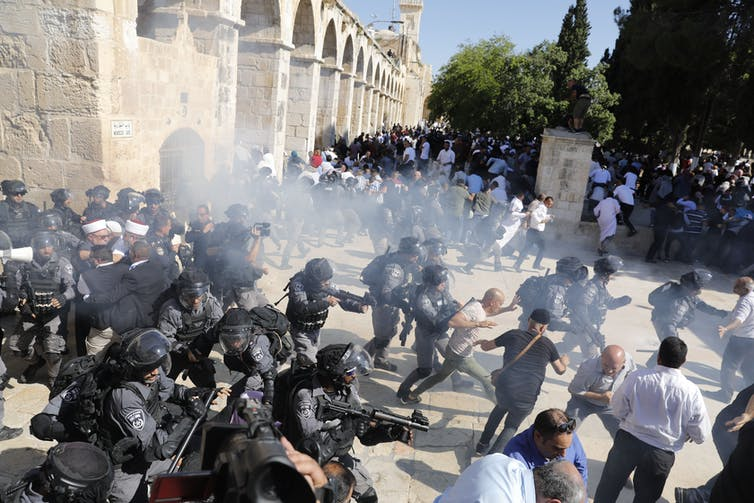 Israeli security forces fire sound grenades inside the al-Aqsa Mosque compound in the Old City of Jerusalem